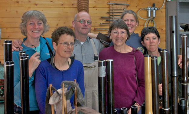 Walking tour leader Rachel Ryan (back left) and members of the group with Martin Doyle (back centre) and Gwenn Frin (back right) among a forest of wooden flutes at Martin's workshop in County Clare.